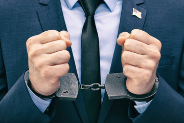White man in handcuffs in hand with USA flag pin on his chest