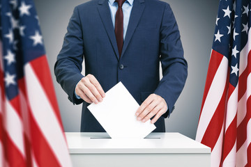 Male in suit holding ballot paper in hand and throwing it into election box with USA flag on background