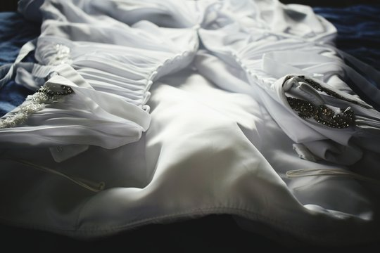 Close-Up Of Wedding Dress On Bed
