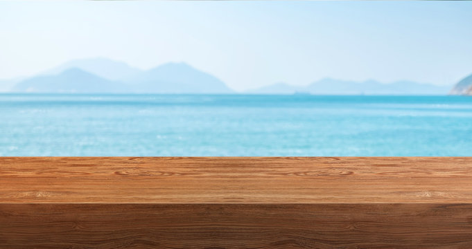 Empty plank wood table with blur blue sky and sea mountain bokeh background,Mock up template for display or montage of product or content use as banner in social media ads