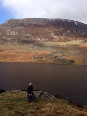 Wall Murals Deep brown Man Sitting At Lake Against Sky