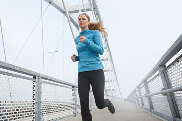 Blond hair female jogging outdoors on cold winter day.
