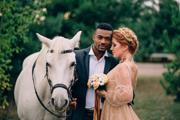 Newlyweds are standing near a white horse in nature, close-up