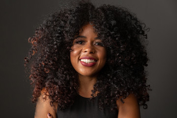 Young afro-american woman with curly hair looking at camera and smiling. Cute afro girl with curly...