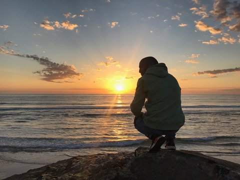 Rear View Full Length Of Man Crouching On Rock At Beach During Sunset