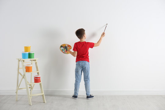 Little child painting on blank white wall indoors