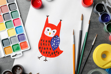 Flat lay composition with child's painting of owl on grey table