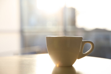 Cup of hot drink on table in morning. Space for text