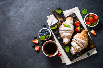 Croissant with fresh berries and cup of coffee on black.