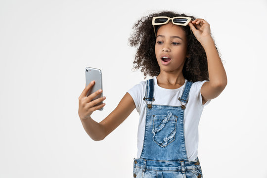 Surprised little african girl kid using mobile phone with sunglasses isolated over white background