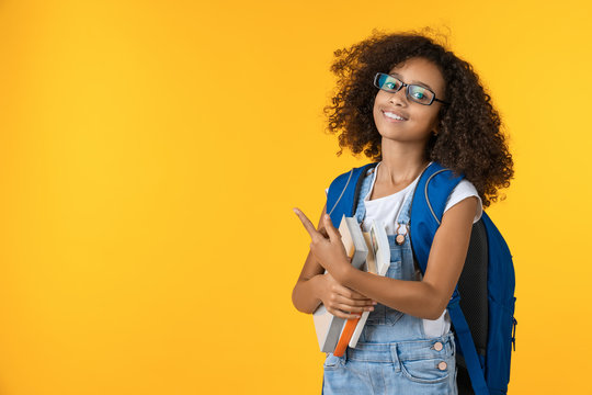 Cute smiling little african american schoolgirl with books on yellow background