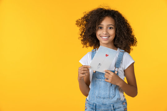 Portrait of beautiful girl holding greeting card isolated on yellow background