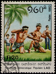 Poster Chicken LAOS - CIRCA 1982: stamp 1.2 Laotian kip (1 kip 20 att) printed by Lao People's Democratic Republic, shows Laotian men practicing wrestling techniques, circa 1982