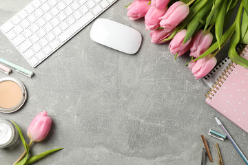Composition with pink tulips on grey background, space for text