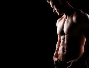 Strong, fit and sporty bodybuilder man over dark background. Sport and fitness.