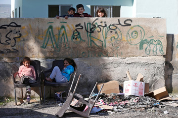 Children smile and pose for a photo outside their home in northern town of Shouneh in the Jordan Valley