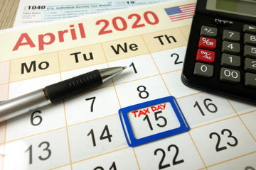 Tax day marked on April 2020 monthly calendar with 1040 form calculator and pen