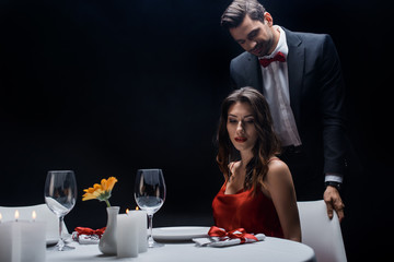 Handsome man standing behind elegant woman at served table isolated on black
