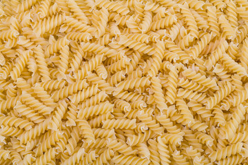 Raw dried extruded fusilli pasta texture. Staple food of Italian cuisine. Culinary background from short uncooked helical pastas for cooking side dishes. Use for recipe, packaging design, gastronomy.