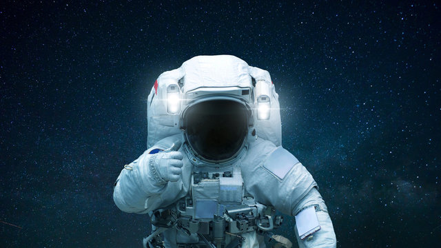 Spaceman in open space with hand shows like. Astronaut travels in space against the background of stars.