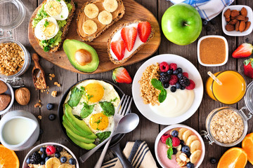 Healthy breakfast table scene with fruit, yogurts, smoothie bowl, oatmeal, nutritious toasts and...