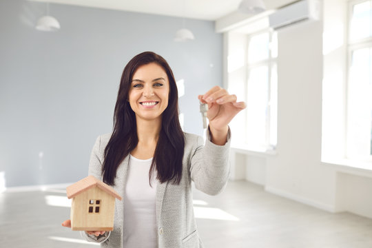 Realtor agent is a realtor with keys in hand against the background of a white real estate room apartment home.