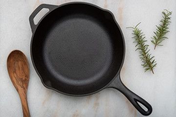 Cast Iron frying pan with spoon on white background with Rosemary Sprigs