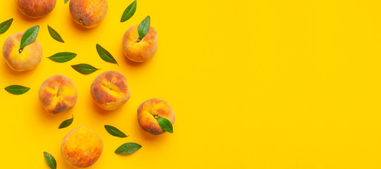 Flat lay composition with peaches. Ripe juicy peaches with green leaves on yellow background. Flat lay, top view, copy space. Fresh organic fruit, vegan food. Juicy Fruit Background