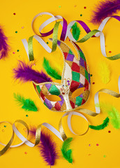 Foto op Canvas Carnaval Festive, colorful mardi gras or carnivale mask and accessories over yellow background. Party invitation, greeting card, venetian carnivale celebration concept. Flat lay, top view, copy space