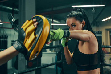 Athletic woman during fight training on boxing ring wearing green bandages on hands, punching exercises with coach