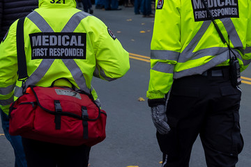 Two men dressed in bright reflective yellow jackets with medical first responder and a large x in reflective print on the backs of their coats. There's a red first aid bag on the attendant's shoulder. Fotomurales
