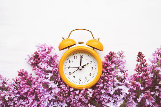 Yellow alarm clock and bouquet of pink lilacs on a white surface, top view. Hello spring, spring time, conceptual image