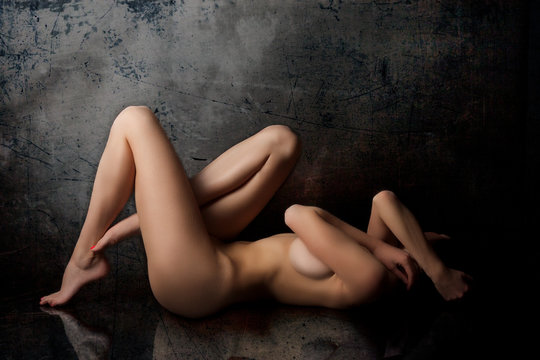 Side View Of Naked Woman Lying Against Wall