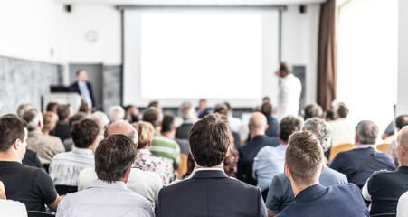 Wall Mural - I have a question. Group of business people sitting at the chairs in conference hall. Businessman standing up asking a question. Conference and Presentation. Business and Entrepreneurship.