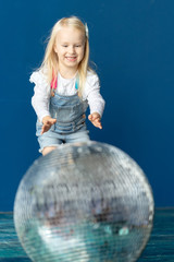 Happy toddler blonde girl havig fun while rolling giant disco ball on the floor. 3 year-old caucasian girl playing with big glitter ball