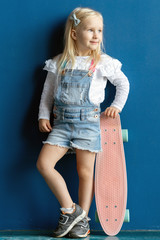Full length portrait of happy 3 years old toddler girl holding pink plastic skateboard while standing against blue wall