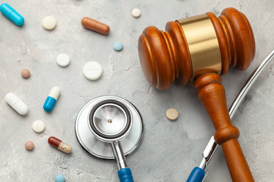 Judge gavel and stethoscope with pills. The law in medicine, the sentence on medical negligence.