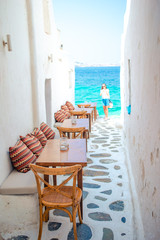 Benches with pillows in a typical greek outdoor cafe in Mykonos with amazing sea view on Cyclades islands
