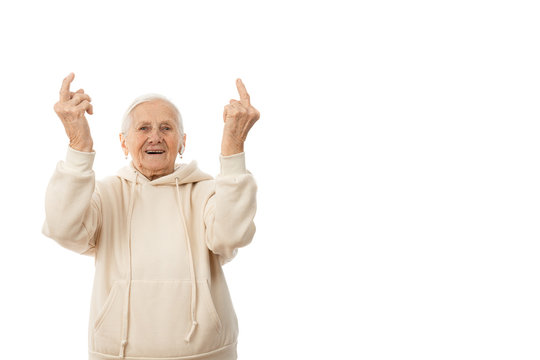 Attractive old woman in beige hoodie, with wireless white headphones showing middle finger, doing fuck you bad expression, provocation and rude attitude, looking at the camera isolated over white