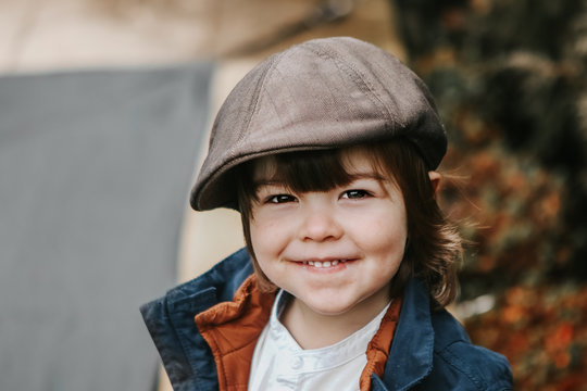 Closeup portrait of cute little smiling toddler boy with long hair in brown cap outdoors. Retro or vintage style.  Copy space.