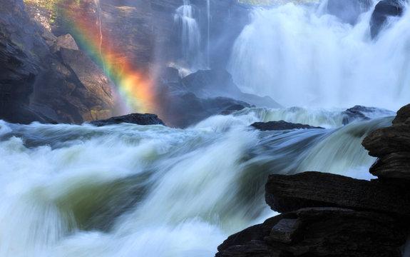 Raging river creates rainbow where steam meets the sunlight.