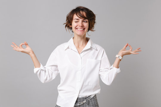 Funny young business woman in white shirt posing isolated on grey background. Achievement career wealth business concept. Mock up copy space. Hold hands in yoga gesture, relaxing meditating, blinking.