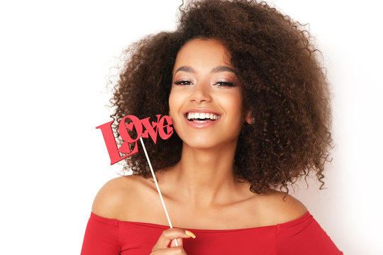 """Beautiful afro-amercian woman in red blouse and stick with """"LOVE"""" is ready for Valentines."""