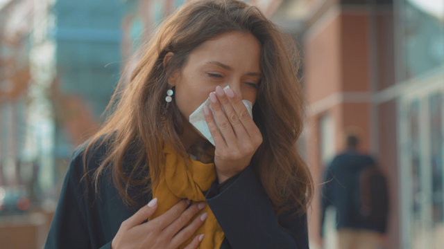 Bad look young woman stand sneezing coughs feel sick at outdoor fever cold allergy city beautiful disease female nose lady runny tissue air pollution adult illness district slow motion