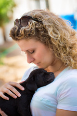 Woman lovingly holds sleeping black labrador puppy on her chest