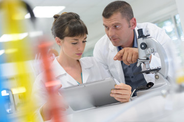 man and woman are in lab using a tablet