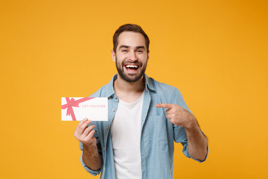 Laughing young man in casual blue shirt posing isolated on yellow orange wall background, studio portrait. People lifestyle concept. Mock up copy space. Pointing index finger on gift certificate.