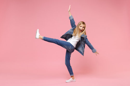 Funny little blonde kid girl 12-13 years old in denim jacket isolated on pastel pink background children studio portrait. Childhood lifestyle concept. Mock up copy space. Spreading hands, rising leg.