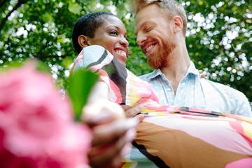 Interracial couple kissing and embracing with flowers and foliage