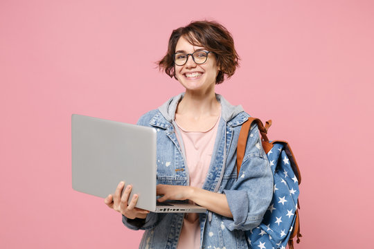 Cheerful young woman student in denim clothes glasses backpack isolated on pastel pink background. Education in high school university college concept. Mock up copy space. Work on laptop pc computer.